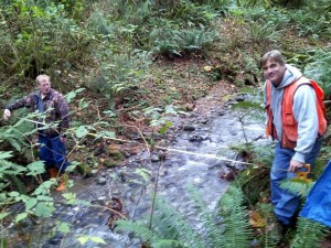 Demonstrating how to measure stream width to understand forest buffers.
